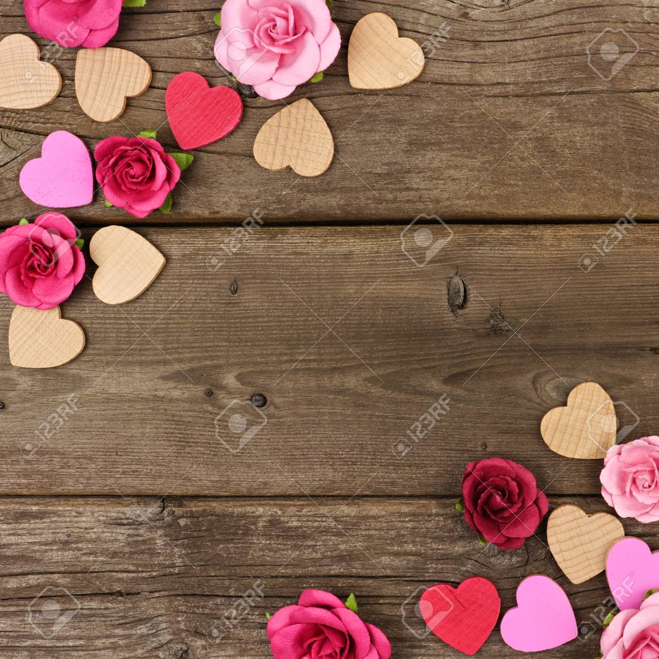 photo valentines day corner frame of wooden hearts and paper roses against a rustic wood background with c