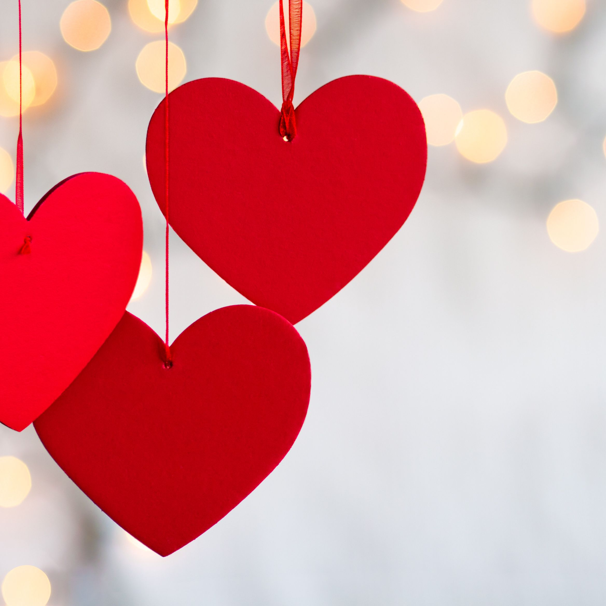 three hanging red hearts on defocused light background 5a32b f a