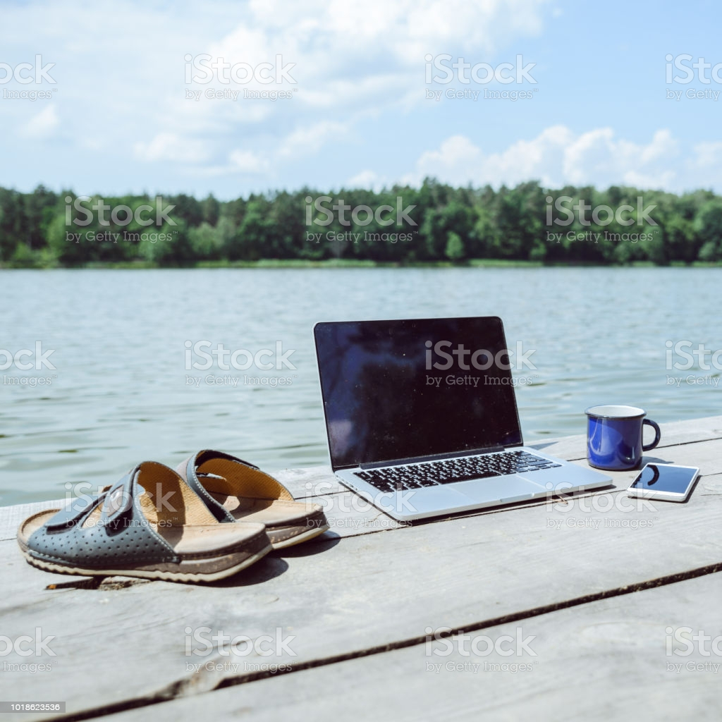 laptop with cup and phone one wooden dock river on background summer picture id